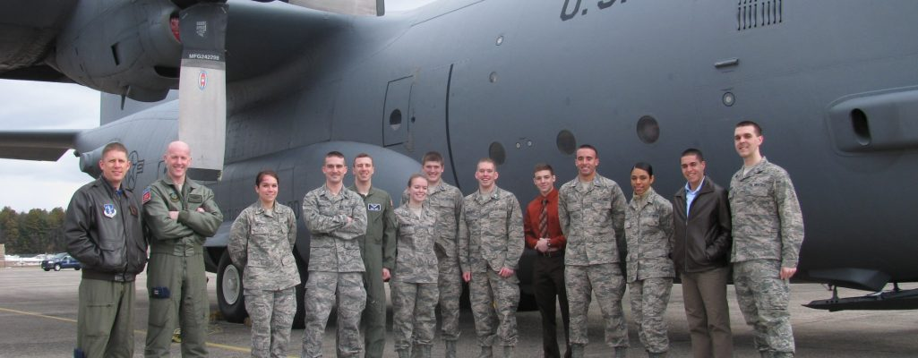 UConn cadets posing for a picture next to an Air Force airplane